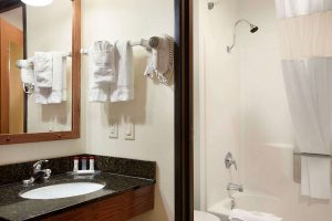 bathroom with sink, vanity mirror, and bath tub at Ramada by Wyndham Wisconsin Dells