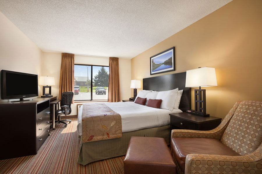 executive king room with arm chair, TV, dresser, and mini fridge at Ramada by Wyndham Wisconsin Dells