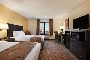 Standard queen bed room across from TV, dresser, mini fridge and work desk with chair at Ramada by Wyndham Wisconsin Dells