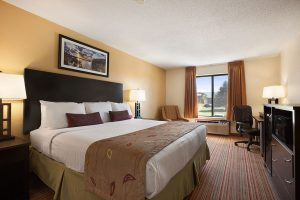 standard king room with bed across from dresser with microwave at Ramada by Wyndham Wisconsin Dells