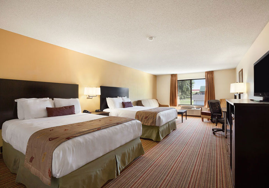 Two queen beds acoross from TV, and dresser with sleeper sofa at Ramada by Wyndham Wisconsin Dells